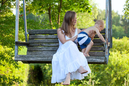 mother helping baby: mother and child on garden swing Stock Photo