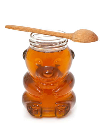 honey in bear-shaped jar isolated on white photo