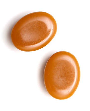 caramel candy: close up of two caramel candies on white background Stock Photo