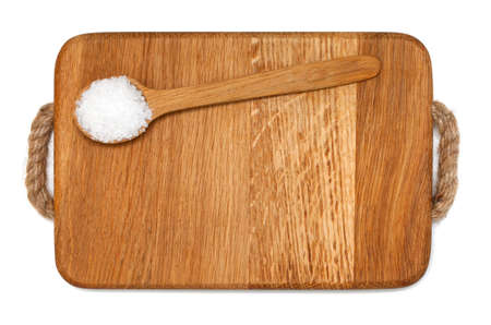 spoonfull of salt on wooden board over white photo