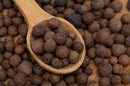 horozontal: whole allspice berries in a wooden spoon Stock Photo