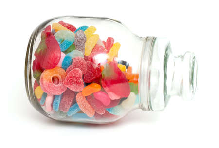 colorful jelly candies in a glass jar over white photo