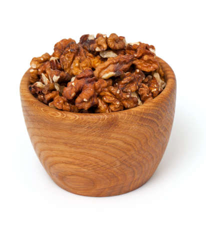 walnuts in a wooden bowl over white photo