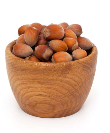 hazelnuts in a wooden bowl isolated on white background Stock Photo - 17324494