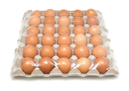 over packed: thirty eggs packed over white Stock Photo
