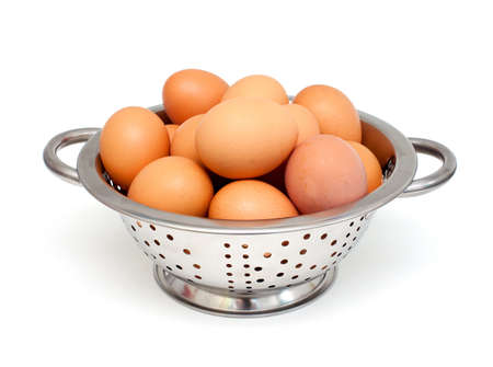 metal colanger with eggs over white Stock Photo - 17324446