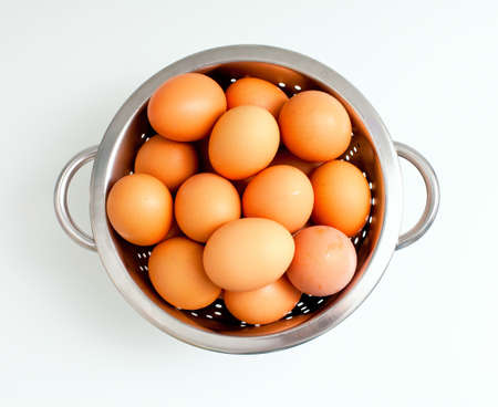 fresh brown eggs in a metal colander on a white background Stock Photo - 17324496