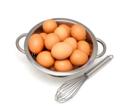 eggs and whisk over white Stock Photo - 17439937