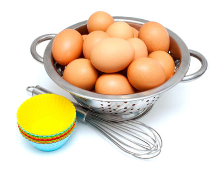 eggs, whisk and cupcake liners over white Stock Photo - 17439982