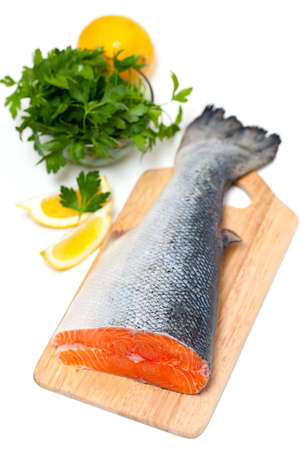 raw salmon with lemon and parsley over white photo
