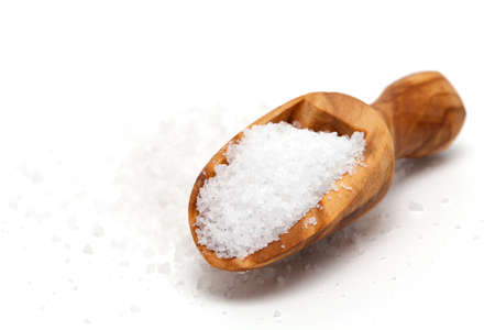 salt in wooden scoop isolated on white background photo