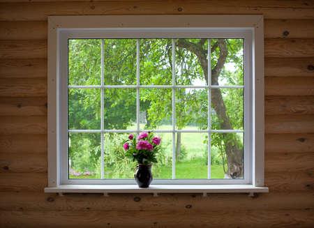peony flowers on wood log house window-sill