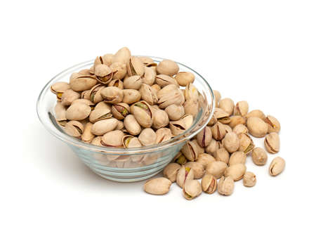 pile of pistachio nuts in a glass bowl on white background photo