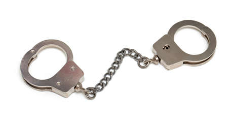 miniature handcuffs isolated on white background photo