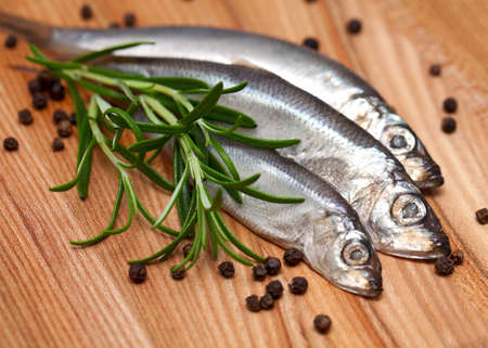 sprat fish and rosemary on wooden table photo