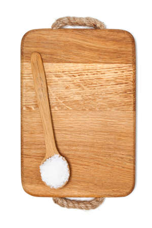 spoonfull of salt on wooden board and empty space for your text photo
