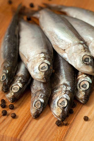 sprat fish with peppercorns on wooden board Stock Photo - 19054860