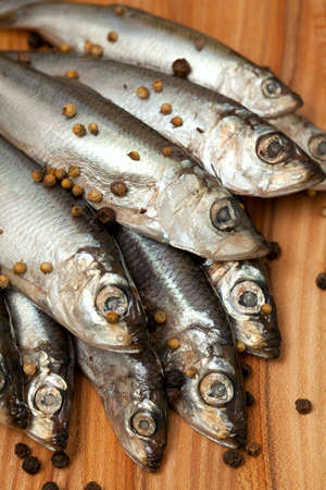 sprat fish with peppercorns on wooden board Stock Photo - 19054853