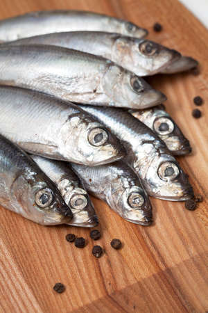 sprat fish with peppercorns on wooden board Stock Photo - 19397936