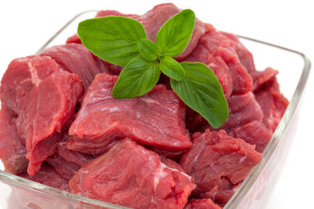 pieces of fresh beef in a glass bowl with oregano isolated on white photo