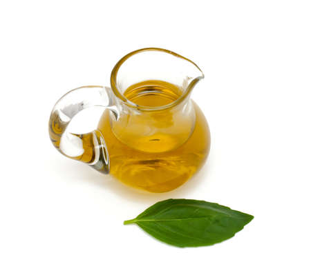 olive oil in a pitcher and leaf of basil photo
