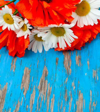 poppies and daisies in bouquet on wooden background photo