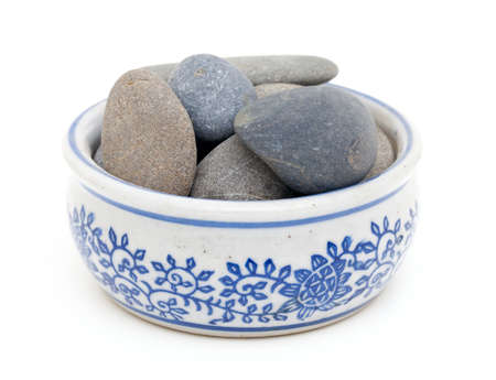 pebbles in a bowl isolated on white background photo