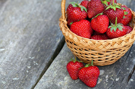 basket with strawberries on wooden surface photo