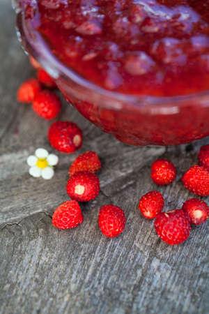wild strawberry jam on wooden background photo