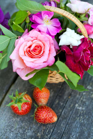 basket with roses and strawberries on garden table on a beautiful summer day photo