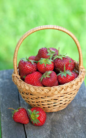 basket with strawberries on wooden garden table photo