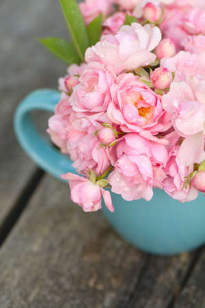 blue cup full of small pink roses