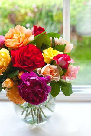 large vase with colorful roses on window sill photo