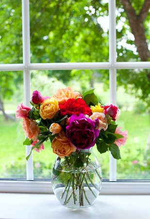 many windows: large vase with colorful roses on window sill