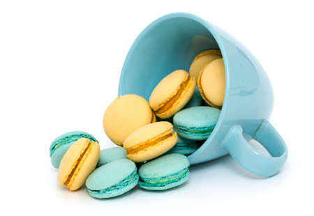 orange and blue macarons in a blue cup over white photo