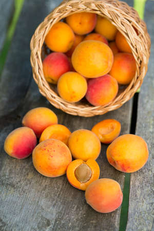 apricots in a basket on wooden background photo
