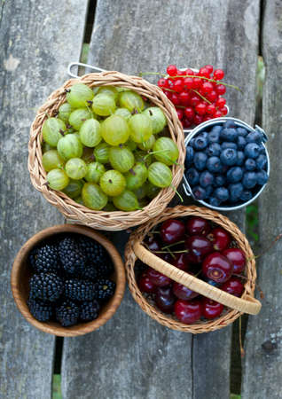 different berries on wooden table photo