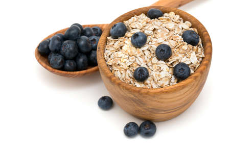 Blueberries and oats over white photo