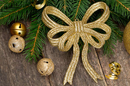 golden ribbon and twig of fir on wooden surface photo