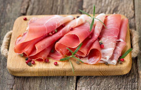 sliced prosciutto on a wooden table photo
