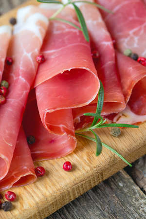 sliced prosciutto on a wooden table Stock Photo