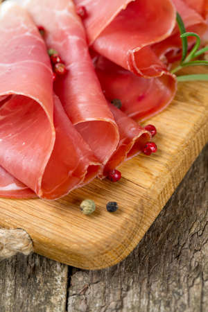 sliced prosciutto on a wooden table Stock Photo - 22831554