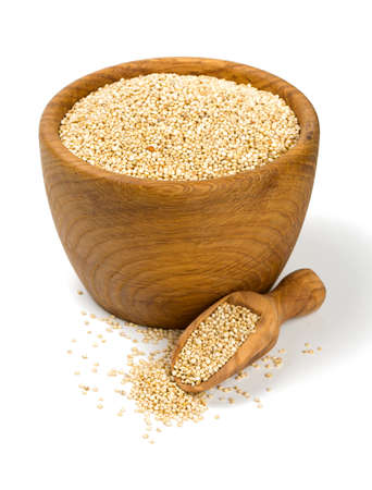 white quinoa in a wooden bowl isolated on white