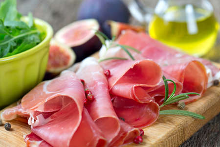 sliced prosciutto on a wooden board photo