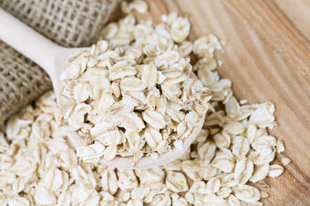 oat flakes in a spoon on wooden surface photo