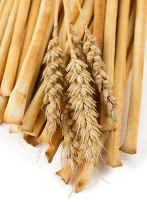 bread sticks and wheat over white photo