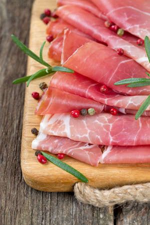 sliced prosciutto on a wooden table Stock Photo - 23639149