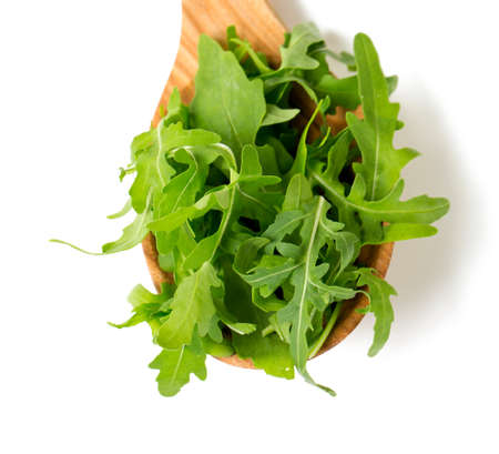rocket lettuce: rucola in a wooden spoon isolated on white