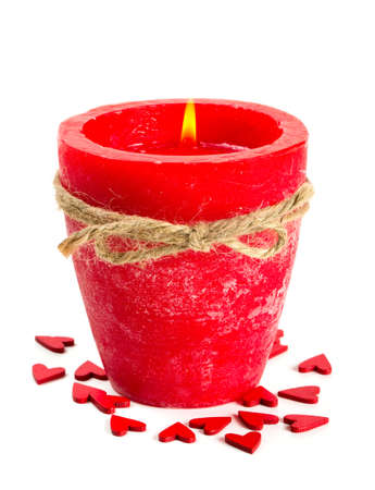 burning love: red candle and wooden hearts isolated on white