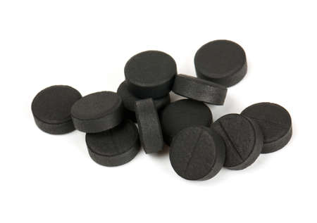 activated: black pills (activated coal) isolated on white Stock Photo